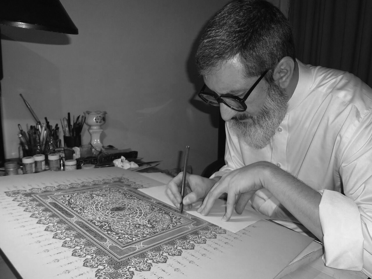 Ayatollah Masoumi Tehrani completing a work of calligraphy of text from the writings of Baha'u'llah, founder of the Baha'i faith