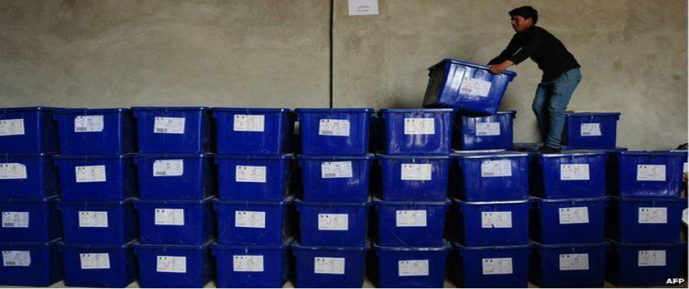 A man stands atop a large stack of blue ballot boxes