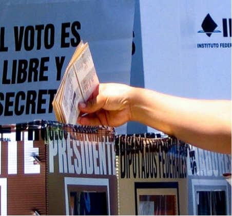 "A hand drops ballot papers into a box marked ""Presidente"""