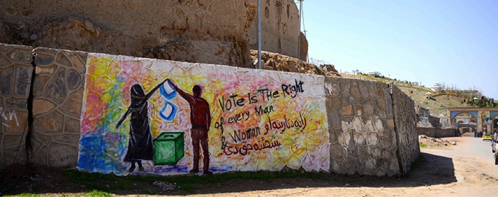 Rainbow-colored elections graffiti reads: Vote is the right of every man and woman