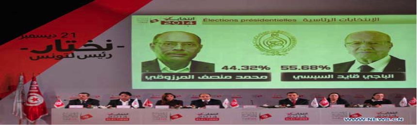 Seven people in business clothing sit on a panel with pictures of Tunisian presidential candidates on the wall behind them