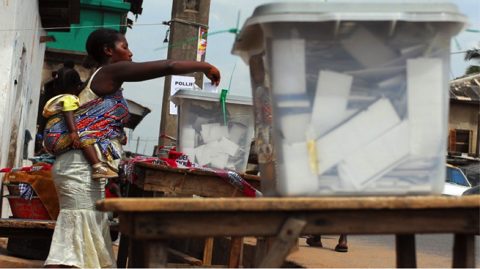 A Ghanaian woman with a baby strapped to her back inserts her ballot into a box