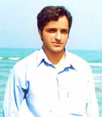Zia Nabavi, dressed in a light blue button-up shirt, stands facing into the sun in front of a body of water.