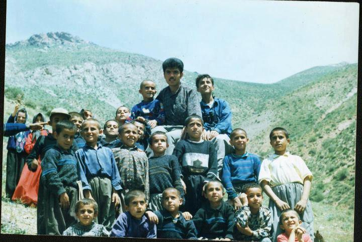 Farzad Kamangar sits amid a crowd of his students, green mountains in the background.